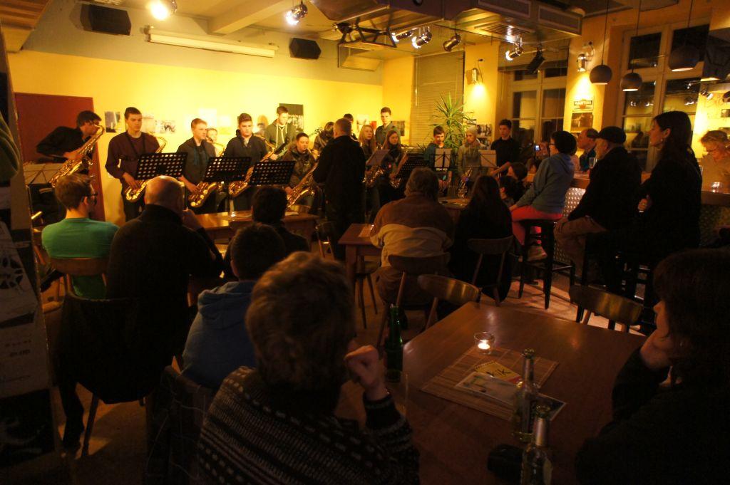 Foto aus der KiK-Kneipe: Musiker vor gelb-beleuchteter Wand spielen vor sitzenden Zuschauern
