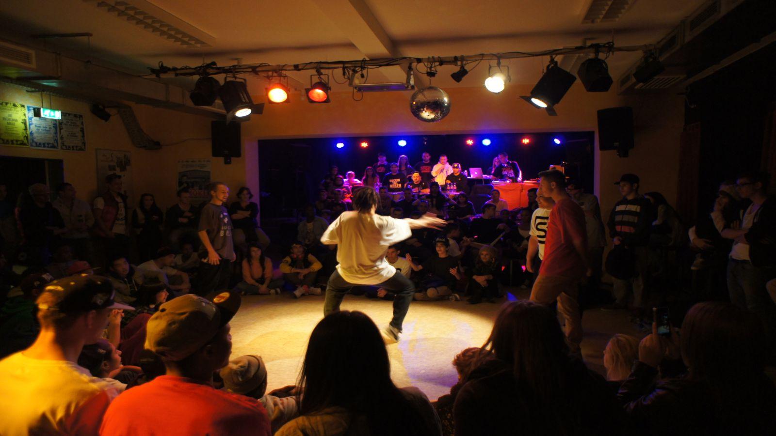 Foto aus dem großen KiK-Saal: bunte Strahler beleuchten eine Tanzfläche mit Hiphop-Tänzern, im Hinergrund beleuchten bunte Dicso-Strahler eine Bühne mit mehreren Personen an einem Tisch. Um die Tänzer sind Zuschauer.
