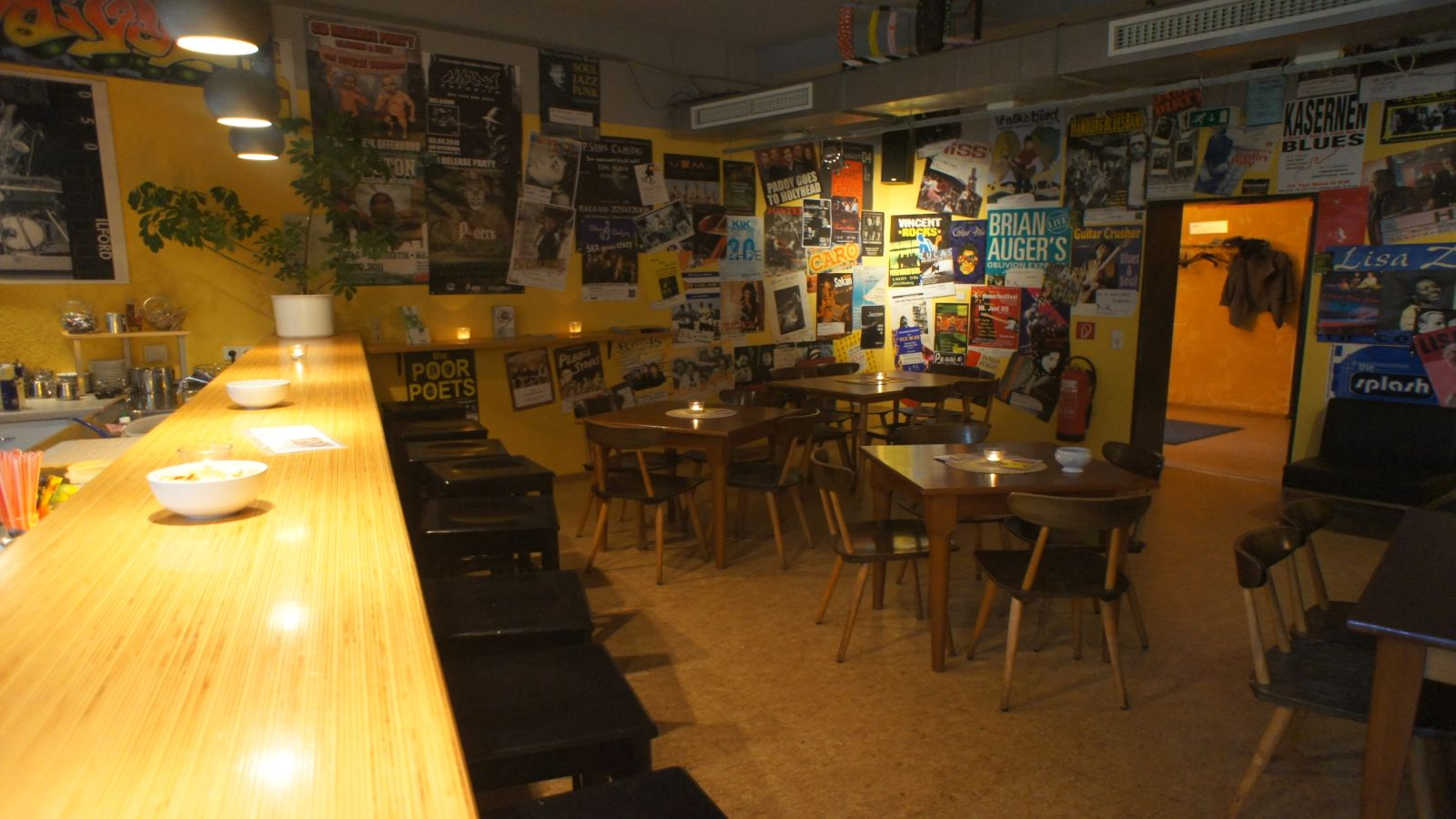Foto: Kik-Kneipenraum mit Theke, Barhockern und Tischen mit Stühlen. Im Hintergrund eine Eckwand mit vielen Plakaten.