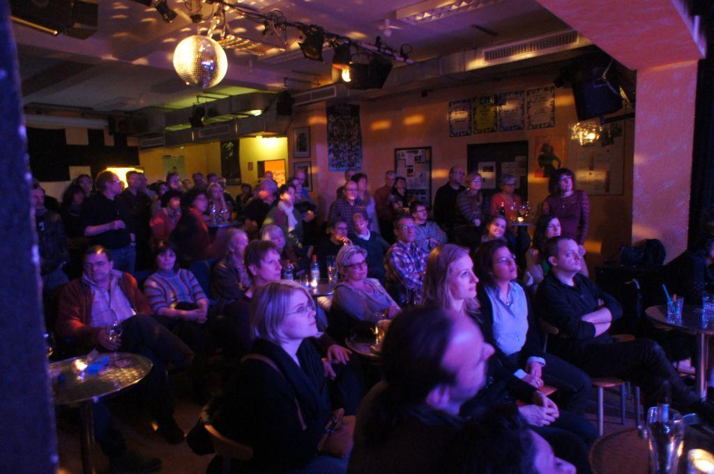 Foto aus dem großen KiK-Saal: bläulich angeleuchtete Zuschauer im Saal, auf Stühlen sitzend, beobachten die Bühne.